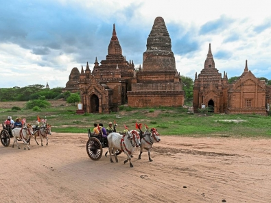 <p>Tourists riding bull carts travel along a road across an ancient Buddhist temple in Bagan on July 5, 2019. (Photo by Ye Aung THU / AFP)</p>